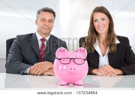 Two Businesspeople Looking At Piggybank