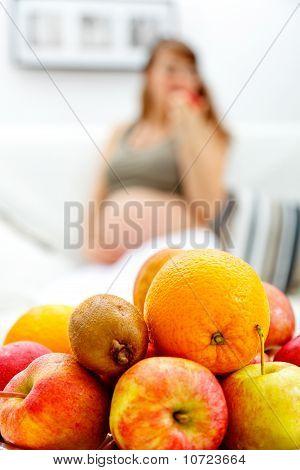 Obstteller auf Tisch und schwangere Frau sitzen auf dem Sofa im Hintergrund