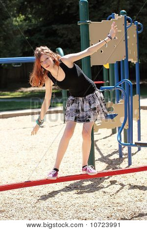 Young Teen Girl Balancing On Red Bar
