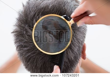 Dermatologist Checking Patient's Hair In Magnifying Glass