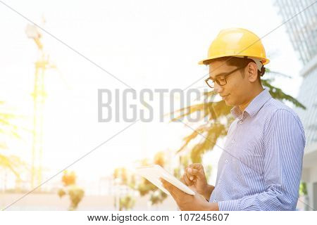 Asian Indian male contractor engineer with hard hat hand holding tablet computer inspecting at construction site, morning sunlight at background.