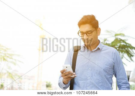 Asian Indian business people texting using smartphone while walking to office, modern urban sunrise view.