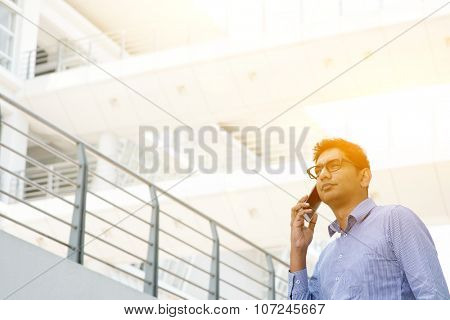Indian businessman calling on phone in front modern office building. Urban view with sun light.