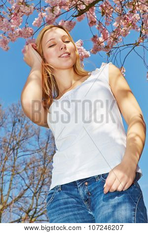 Young blonde woman under blooming cherry tree from below
