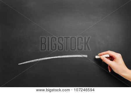 Hand of a teacher drawing white line with chalk on a blackboard