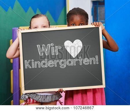 Children holding blackboard with German slogan