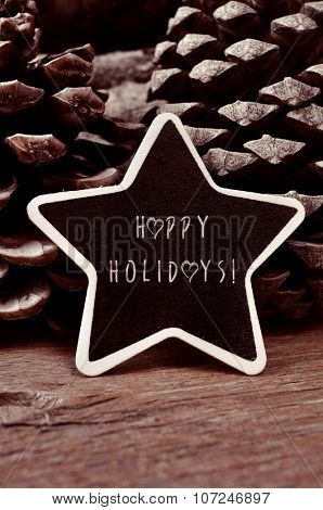 a star-shaped chalkboard with the text happy holidays surrounded by pine cones on a rustic wooden surface