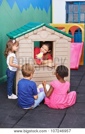 Educator playing theater for children in a playhouse in preschool