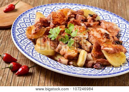 a plate with pulpo a la gallega, a recipe of octopus typical in Spain, spiced with paprika, on a rustic wooden table