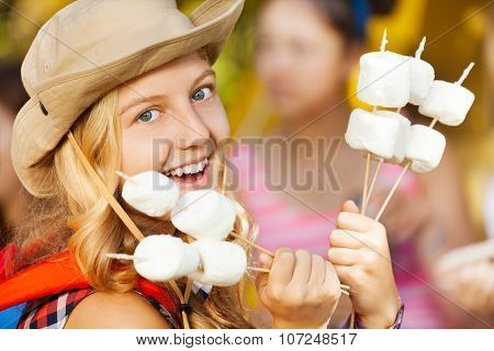 Portrait of girl holding sticks with marshmallow