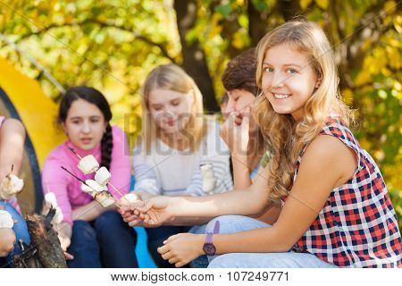 Teens sit on campsite with marshmallow sticks