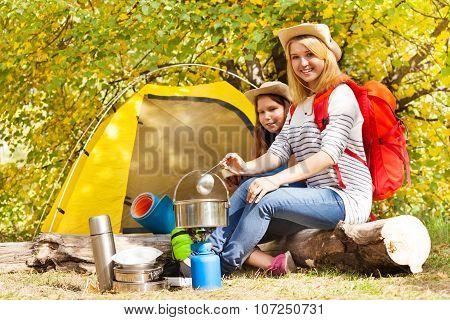 Girls cook soup in metallic pot sitting near tent