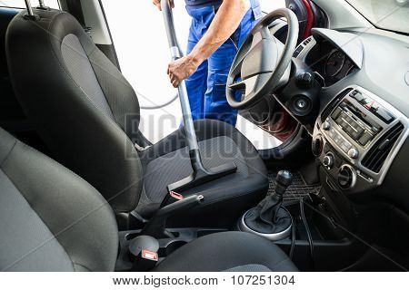 Man Vacuuming Car Seat With Vacuum Cleaner