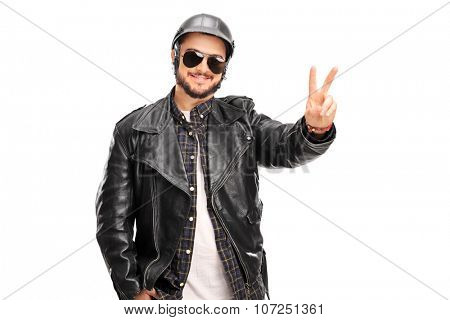 Young cheerful biker in a black leather jacket making a peace hand gesture isolated on white background