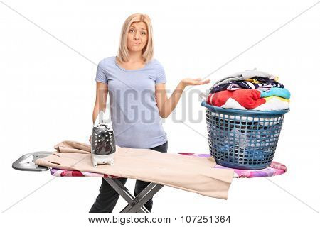 Displeased young woman posing behind an ironing board and gesturing with her hand isolated on white background