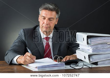 Accountant Checking Invoice With Calculator At Desk