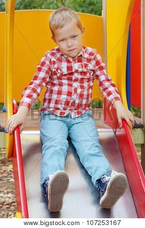 Handsome Little Boy In Shirt Sits On Slide On Playground In Autumn Day