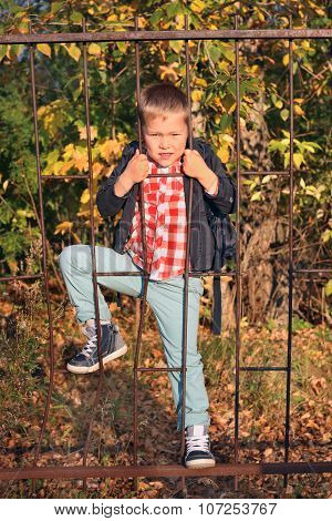 Handsome Boy In Jeans Climbs On Iron Lattice Fence In Autumn Park