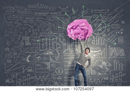 Man lifting in hand big crumpled ball of colorful paper as creativity sign
