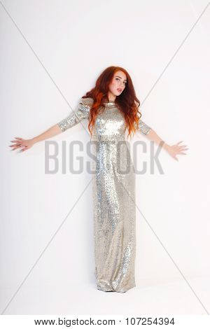 Beautiful Young Girl With Red Hair And Shiny Dress Standing Arms Outstretched Near Wall In Studio