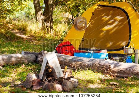 Campsite with tent, backpack and bonfire during beautiful sunny day in the forest