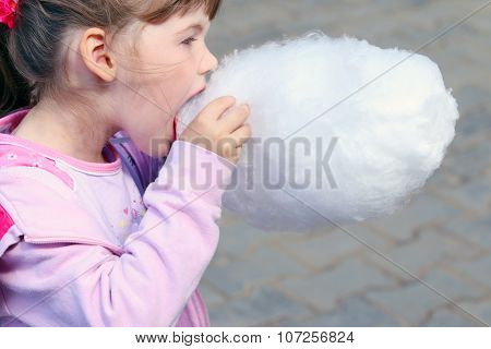 Little Beautiful Girl In Pink Eats Cotton Candy Outdoor At Summer Day