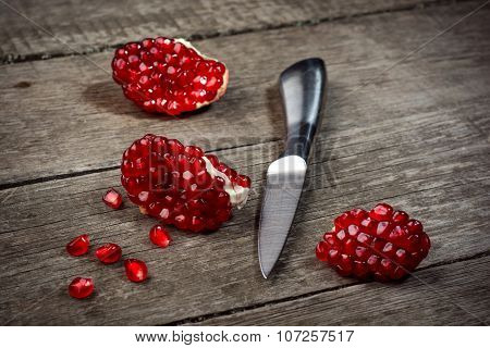 Fresh pomegranate with knife on rustic wooden background.