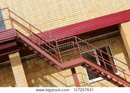 Part Of Modern Building - Yellow Brick Wall, Window And Red Metal Stairs