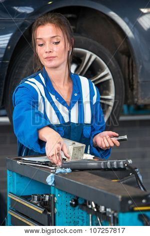 Young woman mechanic, reaching for a torque wrench on a tool trolley in front of a vehicle on a car lift with the car she's working on