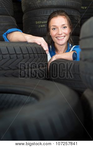 Young, pretty, mechanic, surrounded by stacks of car tyres with varous treads, sizes and compounds, smiling