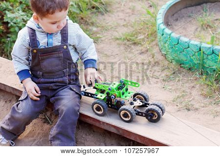 Cute Little Boy In Denim Overalls Playing In Sandbox Green Machine
