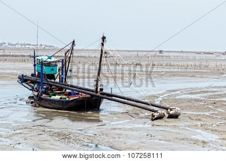 CHONBURI, THAILAND - JUNE 28 2014: Fishing boat at ebb tide waits for the flood tide at Chonburi province on June 28, 2014 in Chonburi,Thailand