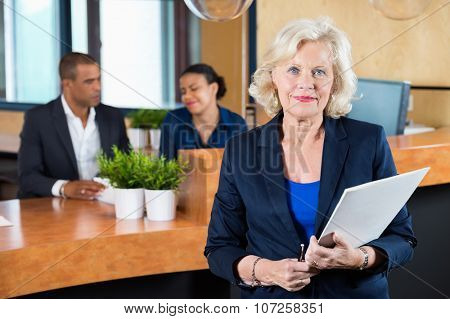 Portrait of confident businesswoman holding file while receptionists working at counter in office