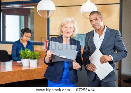 Portrait of confident businesspeople standing while receptionist working at counter in office