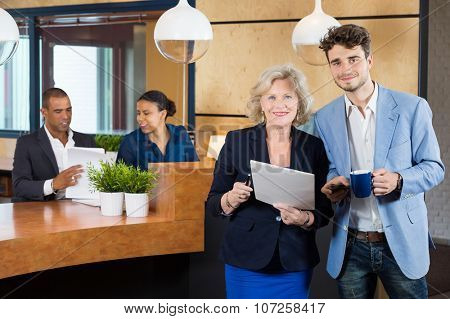 Portrait of confident businesspeople standing while receptionists working at counter in office