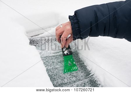 Woman scraping ice and snow