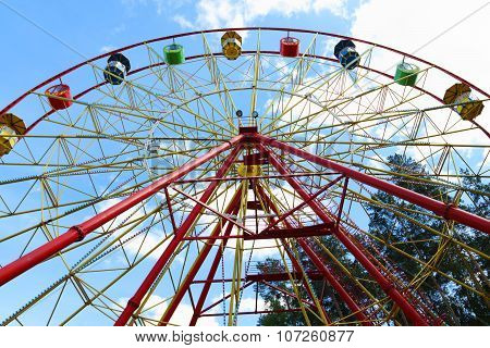 Colorful Ferris Wheel And Tops Of Trees And Blue Sky At Summer Day