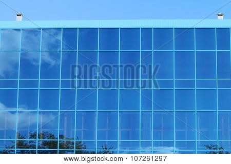 Part Of Modern Building With Blue Windows With Reflection Of Trees At Sunny Day