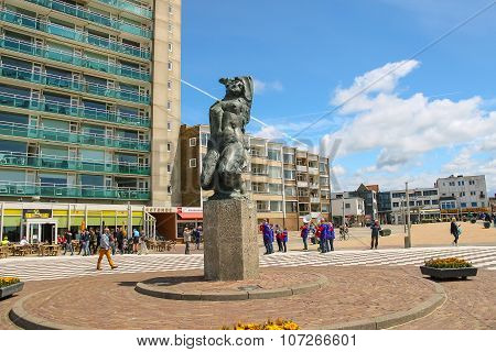 Tourists Walking Next To The Bronze Statue Of Naked Girl On The Boulevard De Favauge. Zandvoort, The