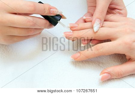 manicure making - female hands, covering enamel