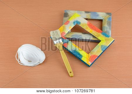 Wooden Frame, Brush And Respirator On Table