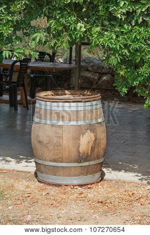 wine barrel in the yard with table and chairs in background