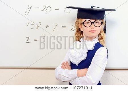 Cute smart schoolgirl in big glasses and academic hat stands at the blackboard. Education.