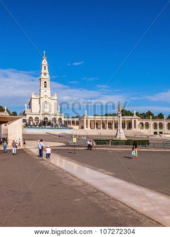 FATIMA, PORTUGAL - SEPTEMBER 9, 2011: The area in front of the Catholic cathedral with tourists and believers. Religious woman kneeling on specially built track