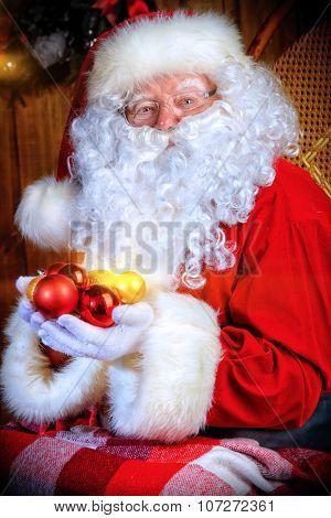 Good old Santa Claus with Christmas balls at his wooden house.