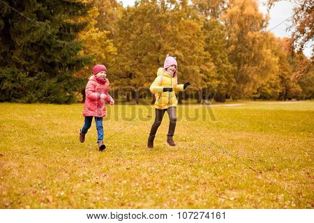 autumn, childhood, leisure and people concept - happy little girls playing tag game and running in park outdoors