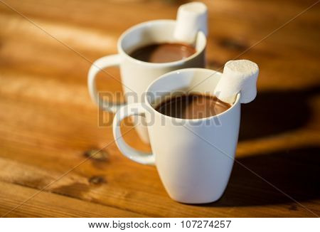 holidays, winter, food and drinks concept - close up of cups with hot chocolate or cocoa drinks and marshmallow on wooden table