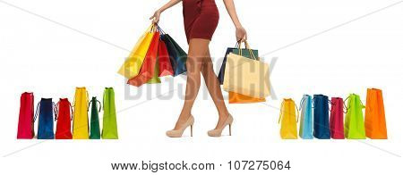 people, sale and consumerism concept - close up of woman in red short skirt and high heeled shoes with shopping bags