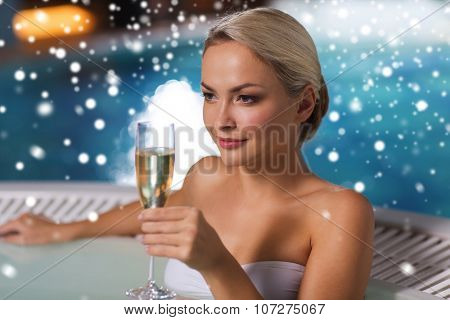 people, beauty, spa, healthy lifestyle and relaxation concept - beautiful young woman wearing bikini swimsuit sitting with glass of champagne in jacuzzi at poolside with snow effect