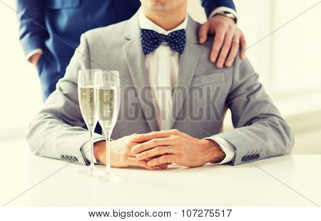 people, celebration, homosexuality, same-sex marriage and love concept - close up of happy married male gay couple in suits and bow-ties with sparkling wine glasses putting hand on shoulder on wedding